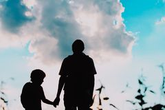 Ather and little son with backpacks travel at sunset nature. Parenting Stock Photo
