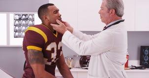 Athete du football d'université ayant l'inju médical de cou de contrôle de médecin Images libres de droits