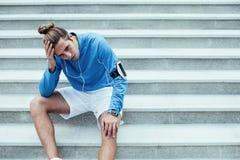 Athlète après la séance d'entraînement d'échec se reposant sur les escaliers sur la rue et tenant sa tête, brassard avec le télép photo stock