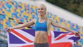 Athlète blond tenant le drapeau de la Grande-Bretagne et se réjouissant la victoire en concurrence banque de vidéos