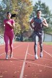 Athlète Couple Sprinting sur la voie courante images stock