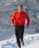 Athlète courant dans la neige Photographie stock libre de droits