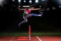 Athlète déterminé de jeune femme sautant au-dessus de l'des obstacles photographie stock libre de droits