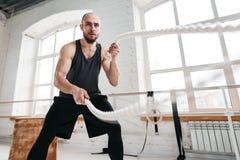 Athlète d'homme d'ajustement employant des cordes de bataille pour s'exercer à la salle de gymnastique légère image stock