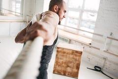 Athlète d'homme d'ajustement employant des cordes de bataille pour s'exercer à la salle de gymnastique légère photos libres de droits