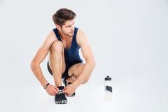 Athlète d'homme avec la bouteille de dentelles de lien de l'eau sur des espadrilles Photo stock
