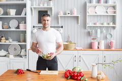 Athlète d'une cinquantaine d'années, tenant une cuvette d'un plat avec de la salade préparée du concombre et de la tomate photos libres de droits