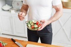 Athlète d'une cinquantaine d'années, tenant une cuvette d'un plat avec de la salade préparée du concombre et de la tomate Nourrit image stock