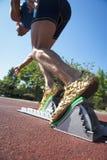Athlète dans des chaussures d'or sur les blocs commençants Photographie stock