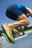 Athlète dans des chaussures d'or sur les blocs commençants Photo stock