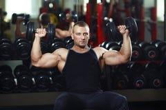Athlète dans la formation de gymnase avec des haltères Photos stock