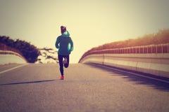 Athlète de coureur de femme de forme physique courant à la route Photographie stock