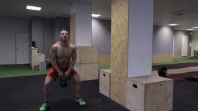 Athlète de CrossFit exécutant l'oscillation 50fps de kettlebell banque de vidéos