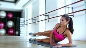 Athlète de femme établissant l'agenouillement sur un tapis de gymnase soulevant sa jambe vers l'arrière dans le ciel clips vidéos