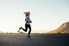 Athlète de femme courant sur la route photos libres de droits