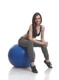 Athlète de femmes s'asseyant sur une bille de forme physique Image stock