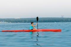 Athlète de fille dans un kayak Photographie stock libre de droits