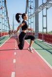 Athlète de jeune femme dans l'habillement de sport sautant pendant la séance d'entraînement images stock