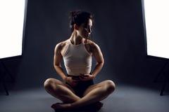 Athlète de jeune femme dans les culottes noires de haut-taille et le dessus blanc se reposant en position de lotus sur le planche Photos stock