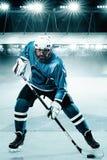 Athlète de joueur de hockey de glace dans le casque et gants sur le stade avec le bâton Tir d'action Concept de sport photographie stock libre de droits