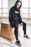 Athlète en sueur détendant après séance d'entraînement intense de crossfit au gymnase images stock