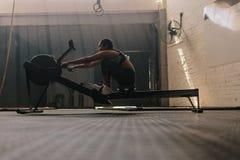 Athlète féminin à l'aide de la machine à ramer photographie stock libre de droits