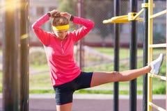 Athlète féminin caucasien concentré Having Legs Muscles étirant des exercices près de l'entraîneur photos stock