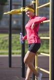 Athlète féminin caucasien sexy de sourire dans l'équipement professionnel posant avec la bouteille d'eau images stock