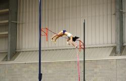Athlète féminin concurrençant dans la chambre forte de poteau Image stock