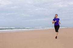 Athlète féminin courant à la plage un jour d'automne Photo libre de droits