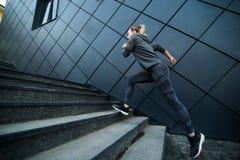 Athlète féminin courant rapidement vers le haut de la séance d'entraînement d'escalier d'escaliers photo stock