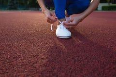 Athlète féminin de coureur attachant les chaussures de course blanches sur la voie courue fin de support Photographie stock libre de droits