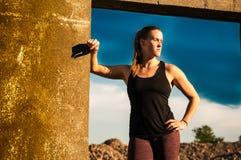 Athlète féminin dur encadré par le bâtiment en béton Image libre de droits