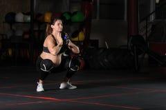 Athlète féminin enceinte faisant des postures accroupies de gobelet photos libres de droits
