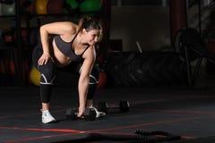 Athlète féminin enceinte faisant le deadlift simple de sumo d'haltère de bras photographie stock