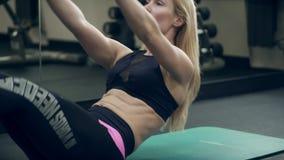 Athlète féminin faisant des craquements abdominaux se trouvant sur le plancher dans le gymnase banque de vidéos
