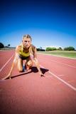 Athlète féminin prêt à fonctionner sur la voie courante image stock