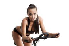 Athlète féminin sexy s'exerçant sur le vélo stationnaire Images stock