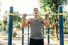 Athlète faisant l'exercice sur la barre horizontale extérieure image stock