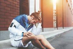Athlète fatigué s'asseyant sur la rue avec des smartwatches et le renversement de brassard avec ses résultats de desserrage de sé images libres de droits