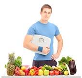 Athlète mâle jugeant une échelle de poids derrière une table pleine de la nourriture Images libres de droits