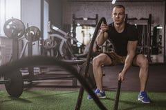 Athlète masculin de crossfit établissant avec des cordes de bataille au gymnase photo libre de droits