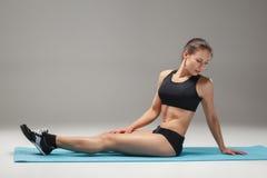 Athlète musculaire de jeune femme s'étirant sur le gris Image stock