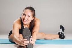 Athlète musculaire de jeune femme s'étirant sur le gris Image libre de droits