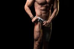 Athlète musculaire Flexing Leg Muscles sur le fond noir Photo stock