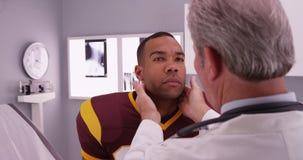 Athlète noir d'université faisant examiner le cou par le médecin photo libre de droits