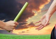 Athlète passant le bâton à l'équipier sur le fond dramatique de coucher du soleil image stock