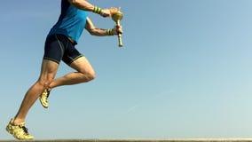 Athlète Running de porteur de flambeau avec le ciel bleu de torche de sport banque de vidéos