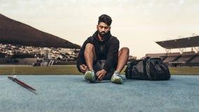 Athlète s'asseyant sur la voie courante portant ses chaussures image stock