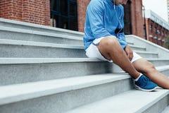 Athlète s'asseyant sur les escaliers, le brassard avec le téléphone portable et les écouteurs avec la musique pour la formation photo libre de droits